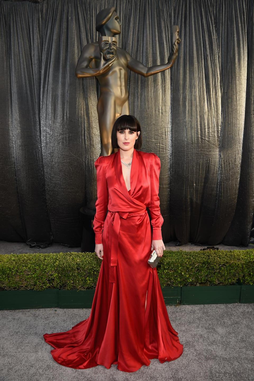 <p>Wearing a red silk gown with a plunging neckline by Ong-Oaj Pairam and Loriblu heels.</p>