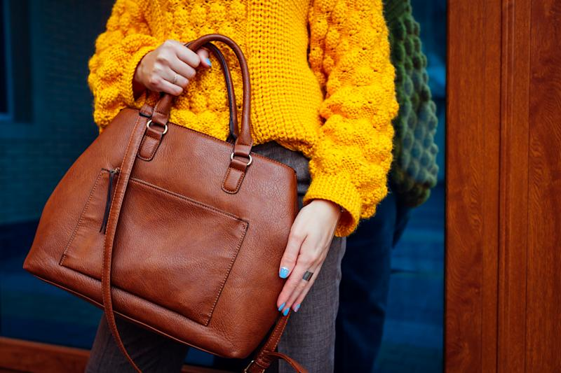 Young woman holding stylish handbag and wearing yellow sweater while looking at watch.