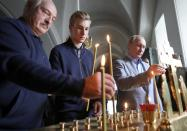 FILE - In this July 17, 2019, file photo, Russian President Vladimir Putin, right, and Belarusian President Alexander Lukashenko, left, and his son Kolya light candles while visiting the Valaam Monastery of the Transfiguration of the Savior on Valaam island, Republic of Karelia, Russia. Lukashenko's years of repression and brutality had all but burned his bridges with the West. Faced with massive protests, he had nowhere to turn for help but to Putin, who has said he was prepared to send police to help stabilize the situation if demonstrations turned violent, but he never made the move. (Mikhail Klimentyev, Sputnik, Kremlin Pool Photo via AP, File)