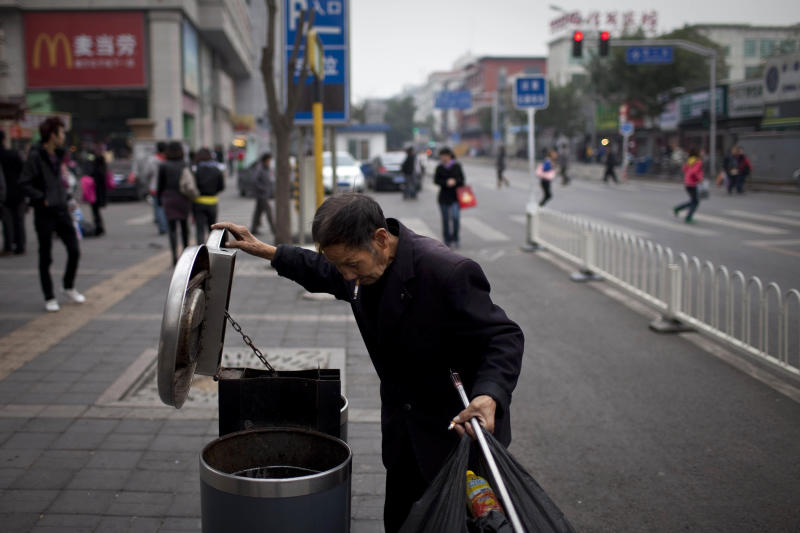 A man checks rubbish bins for recyclable plastic bottles in downtown Beijing, China, Thursday, Oct. 21, 2010. China's rapid growth slowed in the latest quarter as Beijing steered its expansion to a more sustainable level, possibly cutting its contribution to a global recovery. (AP Photo/Alexander F. Yuan)