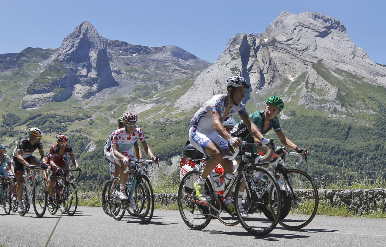 Thomas Voeckler of France, front right, and Sandy Casar of France, front left, lead the breakaway group with Fredrik Kessiakoff of Sweden, wearing the best climber's dotted jersey, as they climb Aubisque pass during the 16th stage of the Tour de France cycling race over 197 kilometers (122.4 miles) with start in Pau and finish in Bagneres-de-Luchon, France, Wednesday July 18, 2012. (AP Photo/Laurent Cipriani)