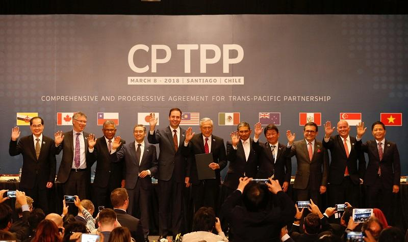 Representatives of members of Trans-Pacific Partnership (TPP) trade deal wave as they pose for an official picture after the signing agreement ceremony in Santiago, Chile March 8, 2018. — Reuters pic