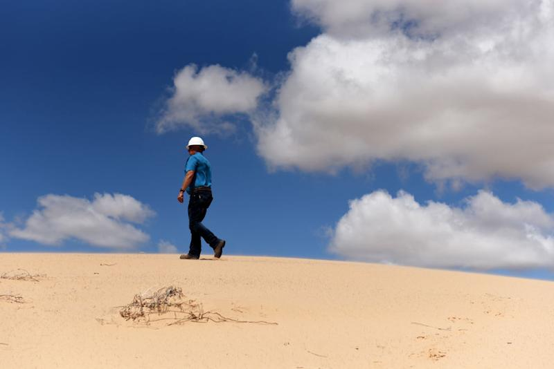 A worker walks along a sand dune at the Hi-Crush Partners LP mining facility in Kermit, Texas, U.S., on Wednesday, June 20, 2018. In the West Texas plains, frack-sand mines suddenly seem to be popping up everywhere. Twelve months ago, none of them existed - together, these mines will ship some 22 million tons of sand this year to shale drillers in the Permian Basin, the hottest oil patch on Earth. Photographer: Callaghan O'Hare/Bloomberg