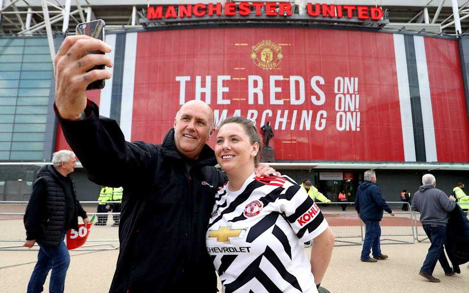 Manchester United fans pose for a selfie - PA