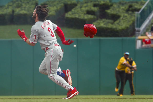 Philadelphia Phillies' Bryce Harper (3) loses his helmet as he digs for second base while Pittsburgh Pirates center fielder Starling Marte, center, throws the ball to second in in the first inning of a baseball game, Sunday, July 21, 2019, in Pittsburgh. Harper was safe with a double. (AP Photo/Keith Srakocic)