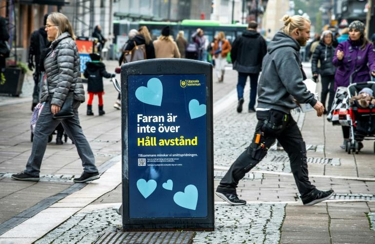 "People walk past a trash can with a sign reading ""The danger is not over - Keep your distance"" in the Swedish city of Uppsala"
