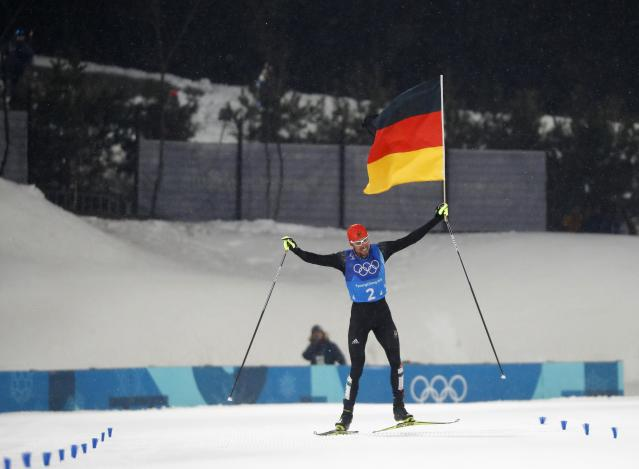 Nordic Combined Events - Pyeongchang 2018 Winter Olympics - Men's Team 4 x 5 km Final - Alpensia Cross-Country Skiing Centre - Pyeongchang, South Korea - February 22, 2018 - Johannes Rydzek of Germany waves the German flag as he approaches the finish line. REUTERS/Kai Pfaffenbach