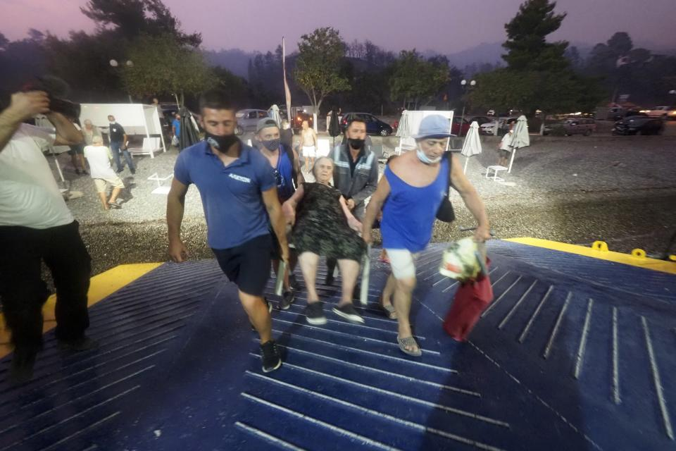 A person is carried in a chair onto a ferry during evacuations in Evia.