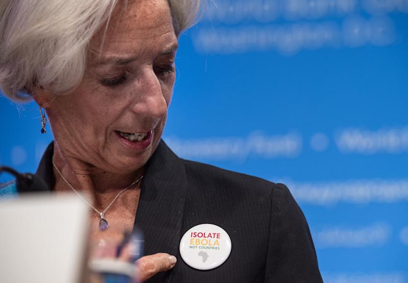 """International Monetary Fund (IMF) Managing Director Christine Lagarde points to a badge reading """"Isolate Ebola Not Countries"""" at a press conference during the annual IMF/World Bank meetings in Washington on October 11, 2014 (AFP Photo/Nicholas Kamm)"""