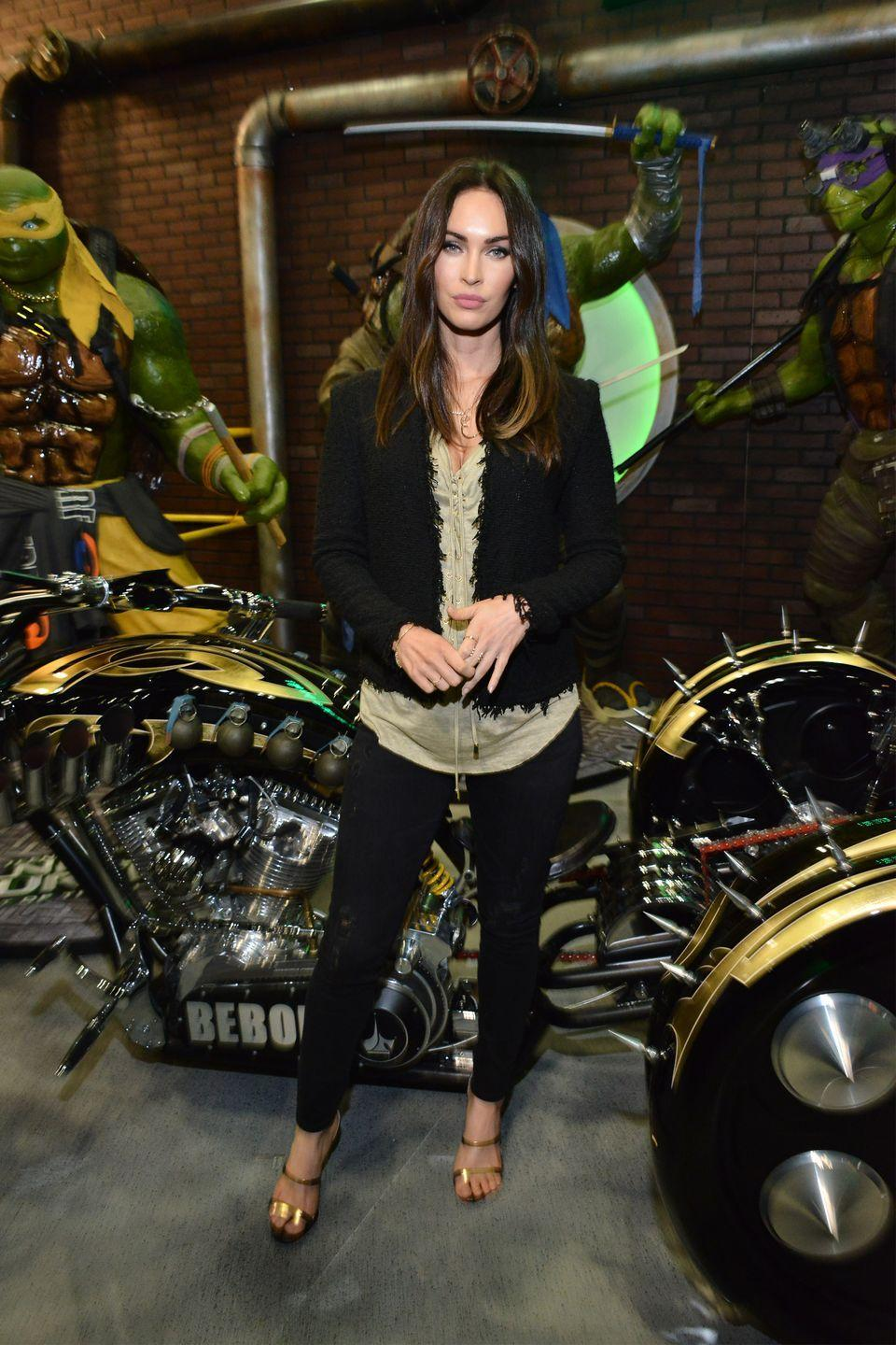 <p>Fox posed for photos before signing autographs at WonderCon 2016 wearing a pair of gold heels, black skinny jeans, a green vest and black jacket. </p>