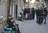 Syrians gather with their belongings in a street in Homs on February 8, 2014 as a UN and Red Crescent humanitarian convoy delivers food and medical aid