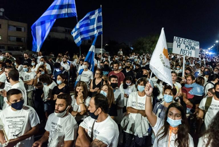 Greek-Cypriots fly flags of Cyprus and Greece during a demonstration at the Deryneia crossing point on the divided island
