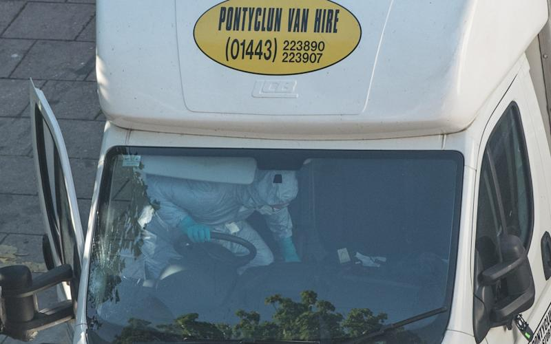 A police forensics officer examines the interior of a van - Credit: Carl Court/Getty