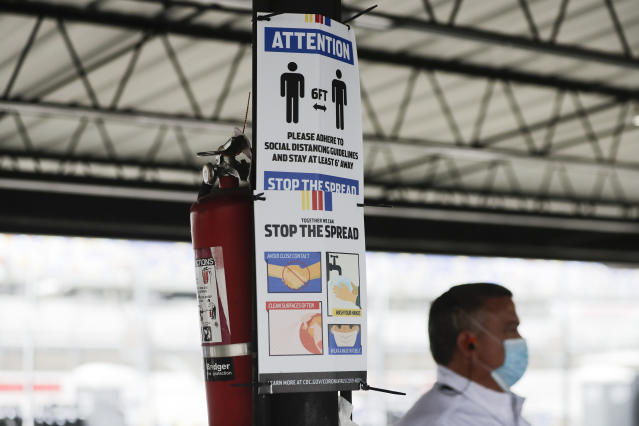A sign reminding people of social distancing and safety measures because of the coronavirus is posted in the garage area before the NASCAR Xfinity series auto race Tuesday, May 19, 2020, in Darlington, S.C. (AP Photo/Brynn Anderson)