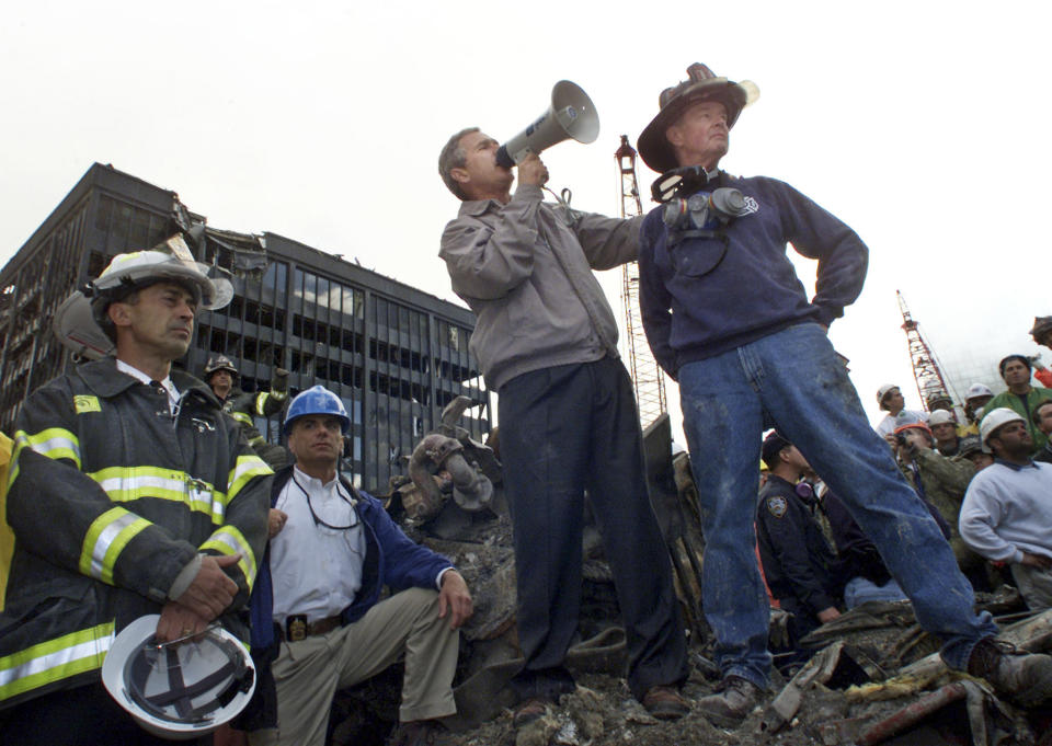 <p>US President George W. Bush talks to retired firefighter Bob Beckwith from Ladder 117 at the scene of the World Trade Center disaster in New York. (Reuters)</p>