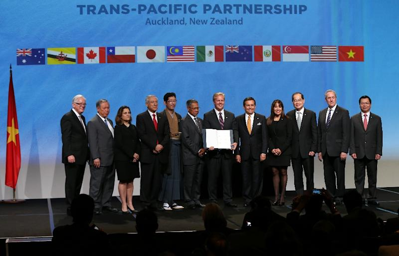 New Zealand Prime Minister John Key (C) and Ministerial Representatives from 12 countries pose for a photo after signing the Trans-Pacific Partnership agreement in Auckland on February 4, 2016 (AFP Photo/Michael Bradley)