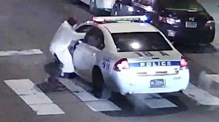 A still image from surveillance video shows a gunman (L) approaching a Philadelphia Police vehicle in which Officer Jesse Hartnett was shot shortly before midnight in Philadelphia, Pennsylvania this Philadelphia Police Department image released on January 8, 2016. REUTERS/Philadelphia Police Department/Handout