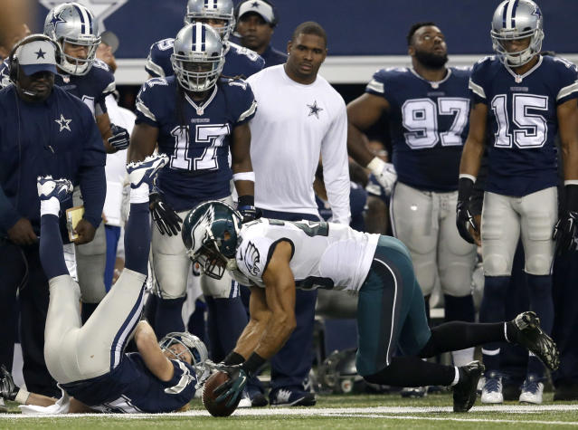 Dallas Cowboys' Cole Beasley, bottom left, and the Cowboys sideline watch as Philadelphia Eagles strong safety Nate Allen (29) recovers a fumble dropped by Beasley during the first half of an NFL football game, Thursday, Nov. 27, 2014, in Arlington, Texas. (AP Photo/Tim Sharp)