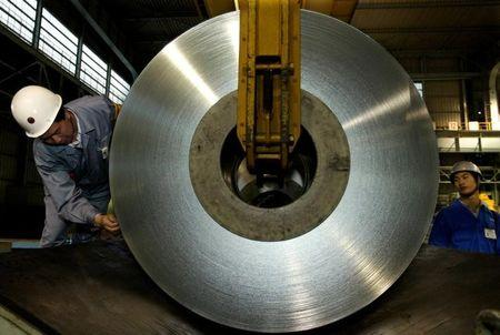 FILE PHOTO: Chinese workers unload a roll of tin plate at a plant on the outskirts of Shanghai