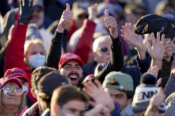 Supporters cheer as cameras point their way as they await President Donald Trump for a campaign stop, Saturday, Oct. 31, 2020, at the Butler County Regional Airport in Butler, Pa. (AP Photo/Keith Srakocic)