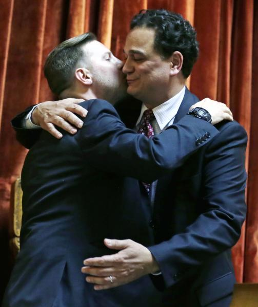 Rhode Island House Speaker Gordon Fox, right, embraces his partner Marcus LaFond after vote to pass a gay marriage bill at the State House in Providence, R.I., Thursday, May 2, 2013. (AP Photo/Charles Krupa)