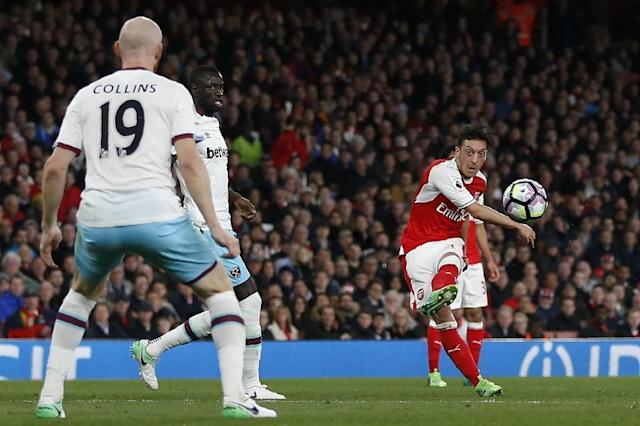 Arsenal's midfielder Mesut Ozil (R) shoots to score the opening goal of the English Premier League football match between Arsenal and West Ham United at the Emirates Stadium in London on April 5, 2017 (AFP Photo/Ian KINGTON)