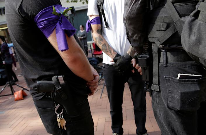 Outside the service, people carryguns to provide security in the event of far-right protesters.