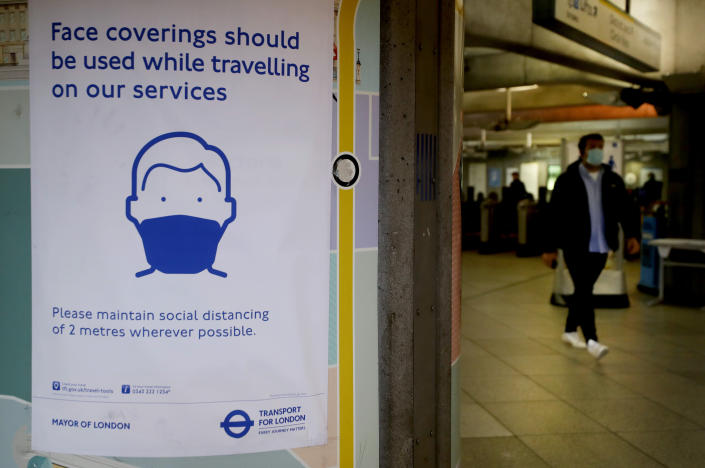 A sign advises travellers to wear face coverings at Westminster Tube Station in London. (AP)