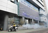 A South Korean health official sprays disinfectant in front of the Daegu branch of the Shincheonji Church of Jesus