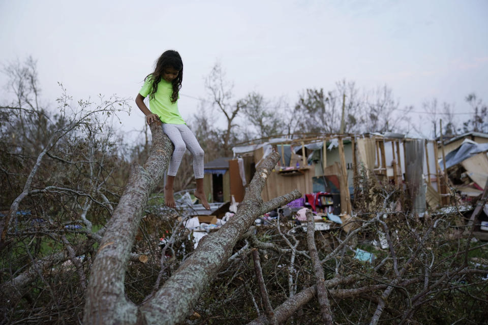 FILE - In this Sept. 4, 2021 file photo, six-year-old Mary-Louise Lacobon sits on a fallen tree beside the remnants of her family's home destroyed by Hurricane Ida, in Dulac, La. Louisiana students, who were back in class after a year and a half of COVID-19 disruptions kept many of them at home, are now missing school again after Hurricane Ida. A quarter-million public school students statewide have no school to report to, though top educators are promising a return is, at most, weeks away, not months. (AP Photo/John Locher, File)