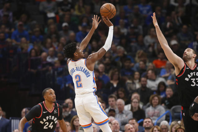 Oklahoma City Thunder guard Shai Gilgeous-Alexander (2) shoots between Toronto Raptors' Norman Powell (24) and Marc Gasol (33) during the first half of an NBA basketball game Wednesday, Jan. 15, 2020, in Oklahoma City. (AP Photo/Sue Ogrocki)