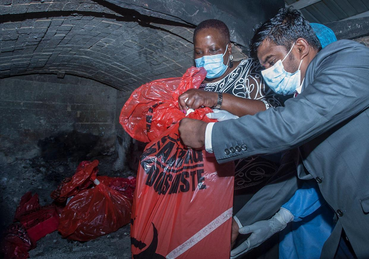 Malawis Health Minister Khumbize Kandodo Chiponda (C) puts packs of expired Covid-19 Astra Zeneca in a pharmaceutical incinerator to destroy them at Kamuzu Central Hospital in Lilongwe on May 19, 2021. - Malawi has destroyed nearly 17,000 doses of the AstraZeneca vaccine that had expired in mid-April, with the health minister blaming