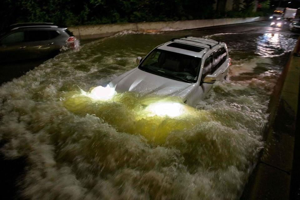 A motorist drives a car through a flooded expressway in Brooklyn, New York early on 2 September (AFP via Getty Images)