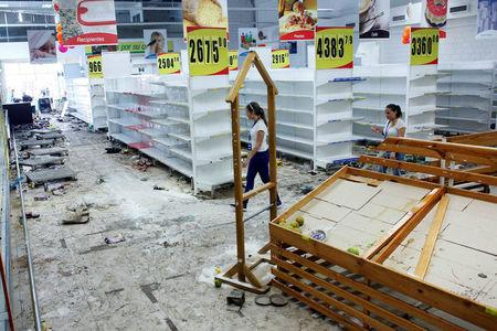 Workers walk next to empty shelves in a supermarket after it was looted in San Cristobal