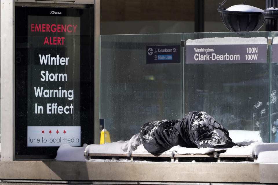 A homeless man Tuesday, Feb. 16, 2021, sleeps at the Chicago Transit Authority's Clark & Dearborn bus station, the morning after a snowstorm dumped up to 18 inches in the greater Chicago area. (AP Photo/Charles Rex Arbogast)