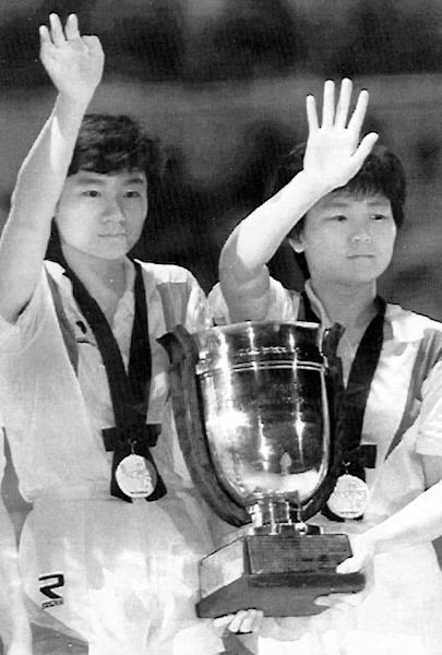 """CORRECTS SPELLING OF NORTH KOREAN PLAYER'S NAME - In this April 30, 1991 photo, South Korea's Hyun Jung-hwa, left, and North Korea's Li Pun Hui, Koreas' first-ever unified team, wave while holding their winning trophy after they defeated China at a world table tennis championships competition in Chiba, Japan. Grudgingly putting aside politics, the intensely competitive Li paired up with her arch rival, South Korean star Hyun, in 1991 as part of the first """"unified Korea"""" team to march into international competition wearing the flag of the Korean Peninsula. (AP Photo/Yonhap) KOREA OUT"""
