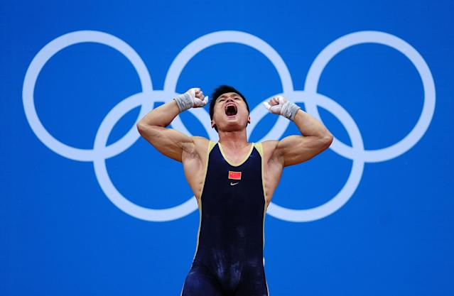 LONDON, ENGLAND - AUGUST 01: Xiaojun Lu of China reacts after setting his second world record of the event by scoring a total of 379 while competing in the Men's 77kg Weightlifting on Day 5 of the London 2012 Olympic Games at ExCeL on August 1, 2012 in London, England. (Photo by Laurence Griffiths/Getty Images)