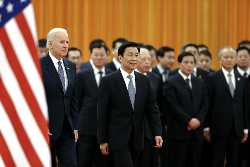 Chinese Vice President Li Yuanchao, right, accompanies U.S. Vice President Joe Biden, left, to view an honor guard during a welcome ceremony inside the Great Hall of the People on Wednesday, Dec. 4, 2013, in Beijing, China. (AP Photo/Lintao Zhang, Pool)