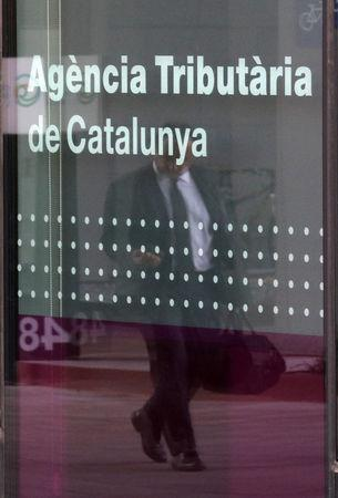 A man is reflected on a glass of the Catalan Tax Agency in Barcelona, Spain, September 18, 2017. REUTERS/Albert Gea