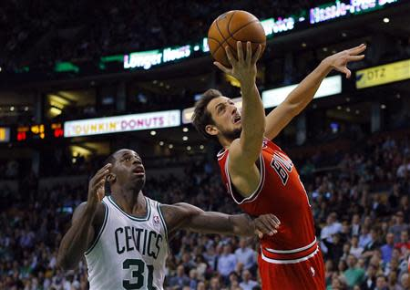 Chicago Bulls guard Marco Belinelli (R) of Italy scores a basket past Boston Celtics forward Brandon Bass in the second half of their NBA basketball game in Boston, Massachusetts February 13, 2013. REUTERS/Brian Snyder