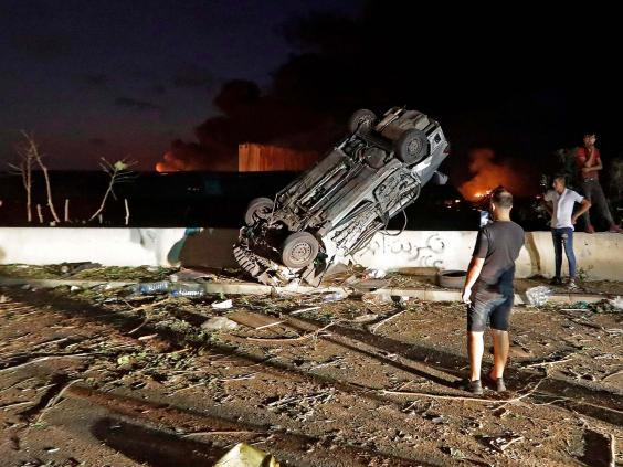 People gather by cars destroyed by the explosion (AFP via Getty Images)