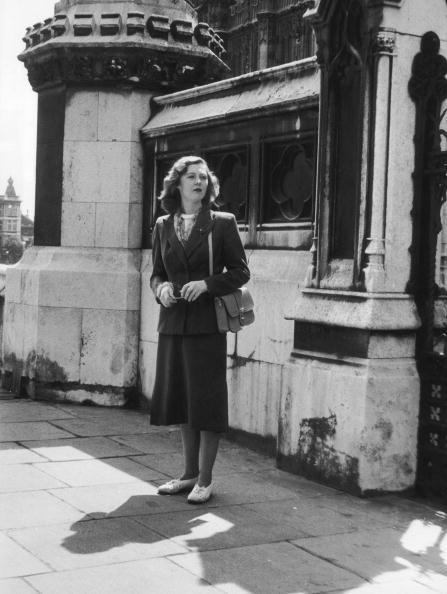 <p>Skirt suits still steal the moment in 1952, updated with a chunky beaded necklace and shoulder bag.</p>