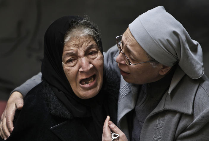 FILE - In this Sunday, Jan. 2, 2011 file photo, an Egyptian Coptic Christian woman, left, is comforted by a Coptic nun, right, as she cries out in emotion following morning mass inside the Saints Church after 21 worshippers were killed in an apparent suicide bombing in Alexandria, Egypt. Despite his rhetoric and promises to uphold the civil nature of Egypt, Shafiq seemed to some Egyptians an odd choice for Christians who suffered attacks under Mubarak's near 30 year-rule, culminating in the bombing of a church in Alexandria that killed 21 people attending a New Year's Even Mass more than a year ago. (AP Photo/Ben Curtis, File)