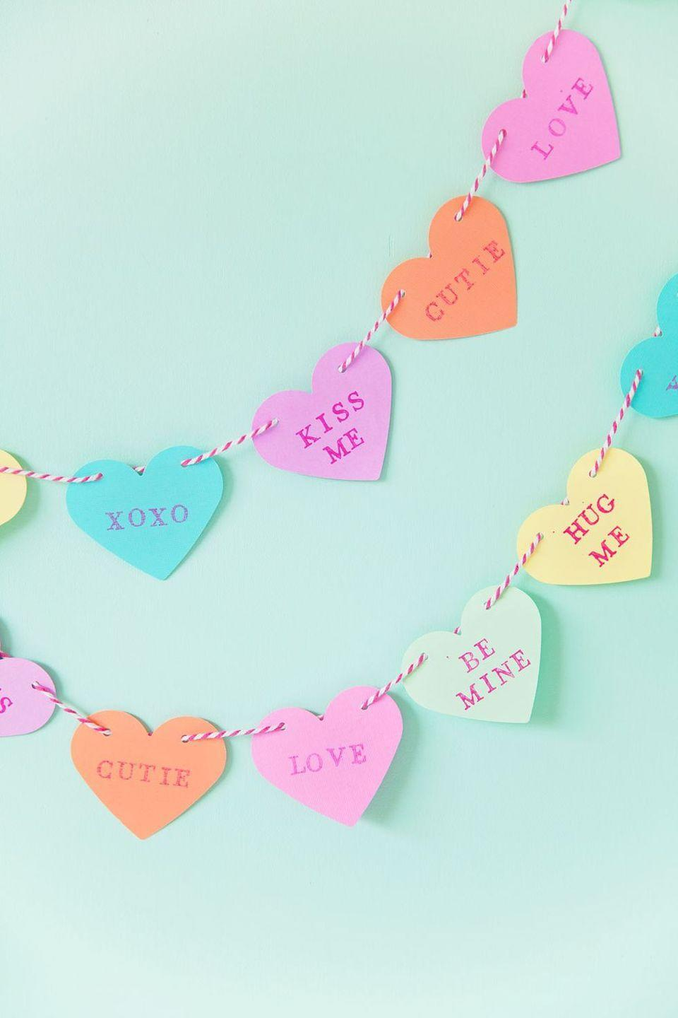 """<p>We love that this garland takes cues from those classic conversation heart candies. Bonus points if you include a few inside jokes of your own amongst the messages!</p><p><strong>Get the tutorial at <a href=""""https://tellloveandparty.com/2017/01/diy-candy-heart-garland.html"""" rel=""""nofollow noopener"""" target=""""_blank"""" data-ylk=""""slk:Tell Love and Party"""" class=""""link rapid-noclick-resp"""">Tell Love and Party</a>.</strong></p><p><a class=""""link rapid-noclick-resp"""" href=""""https://www.amazon.com/Extreme-Variety-American-Crafts-Brights/dp/B00GXG0CVW?tag=syn-yahoo-20&ascsubtag=%5Bartid%7C10050.g.2971%5Bsrc%7Cyahoo-us"""" rel=""""nofollow noopener"""" target=""""_blank"""" data-ylk=""""slk:SHOP BAKER'S TWINE"""">SHOP BAKER'S TWINE</a></p>"""