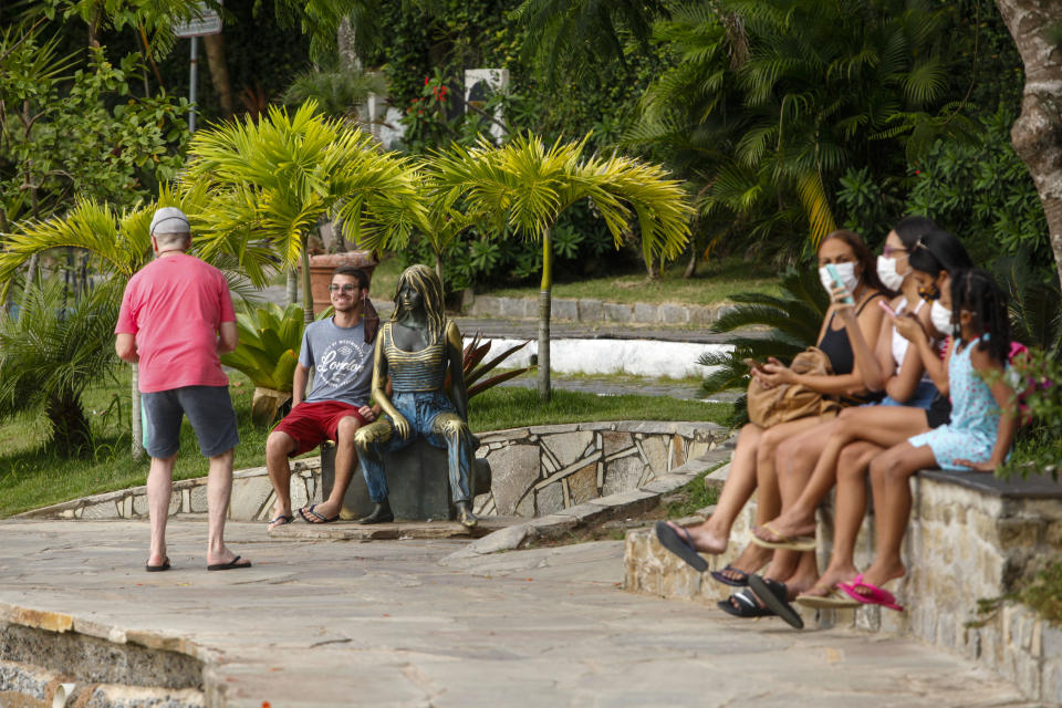 BUZIOS, BRAZIL - DECEMBER 18: Tourists enjoy the weather next to a Brigitte Bardot  statue at Orla Brigitte Bardot after the decision of the Rio de Janeiro State Justice to reverse the closure of the city due to the increase in coronavirus (COVID-19) cases on December 18, 2020 in Buzios, Brazil. According to the judge it was evident the public interest and the serious damage to the order and public economy that the closure of the city would provide.  (Photo by Luis Alvarenga/Getty Images)