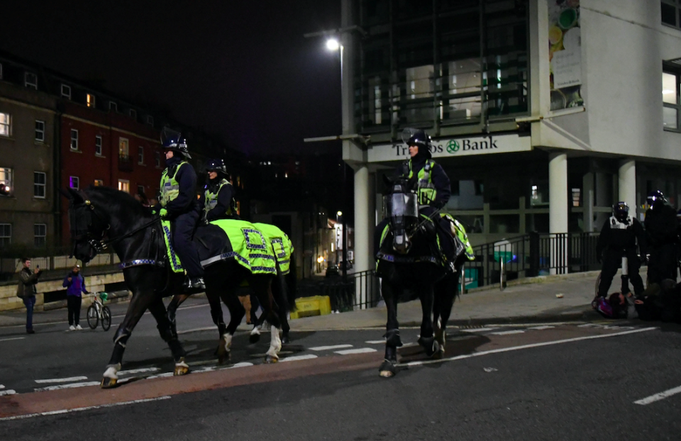 Officers on horseback patrol the streets of Bristol following another night of protests. (SWNS)