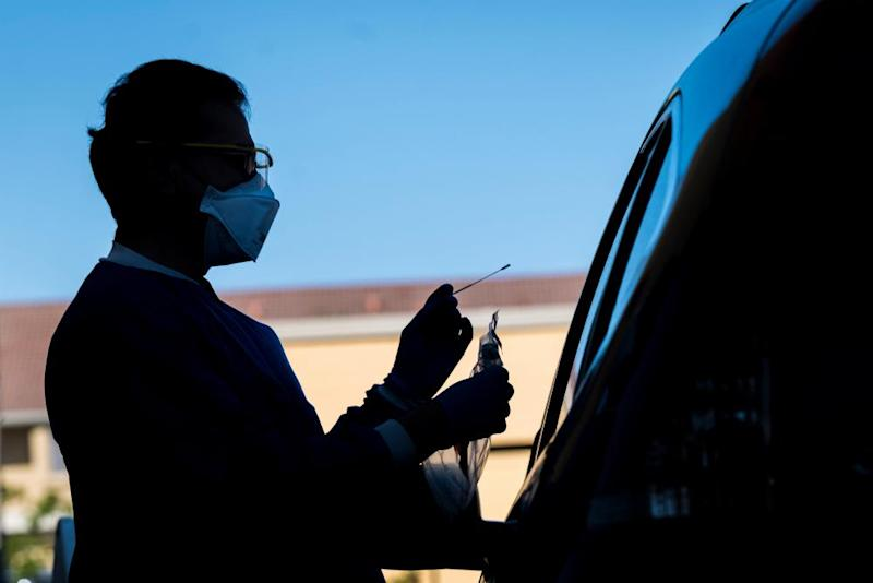 A healthcare worker administers a swab test at a Covid-19 drive-thru testing site in San Pablo, California, on 28 April.