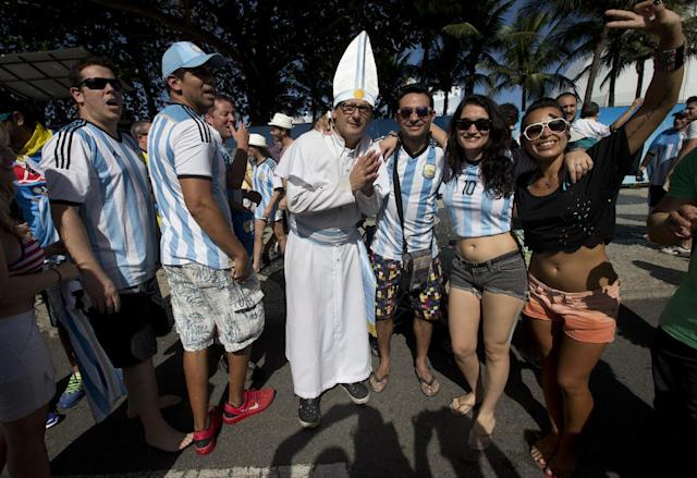 An Argentina soccer fan dressed as Pope Francis poses for photos with other fans gathering to watch the final World Cup match between Argentina and Germany on Copacabana beach in Rio de Janeiro, Brazil, Sunday, July 13, 2014. (AP Photo/Silvia Izquierdo)