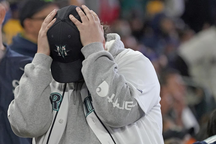 A Seattle Mariners fan reacts after Los Angeles Angels' Jack Mayfield was ruled safe stealing second base after the initial call of out was overturned on review during the sixth inning of a baseball game, Sunday, Oct. 3, 2021, in Seattle. (AP Photo/Ted S. Warren)