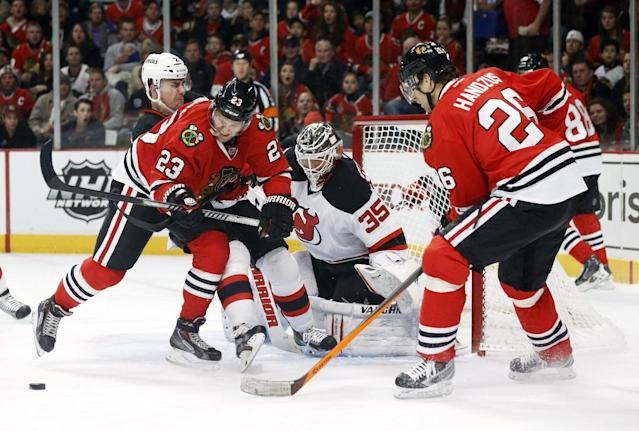 Chicago Blackhawks right wing Kris Versteeg (23) is unable to get a shot on goal while New Jersey Devils defenseman Marek Zidlicky (2) and goalie Cory Schneider defend as Michal Handzus (26) watches during the second period of an NHL hockey game Monday, Dec. 23, 2013, in Chicago. (AP Photo/Charles Rex Arbogast)
